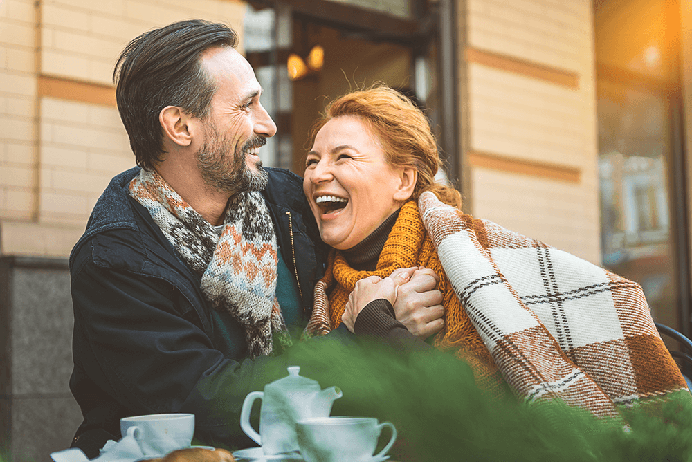 A smiling middle aged man and woman, laughing and enjoying brunch outside