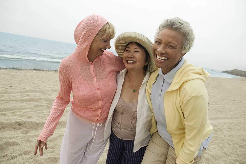 Three smiling older women walking on the beach with their arms around each others' shoulders