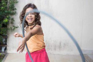 A smiling young girl throwing a hula hoop toward the camera