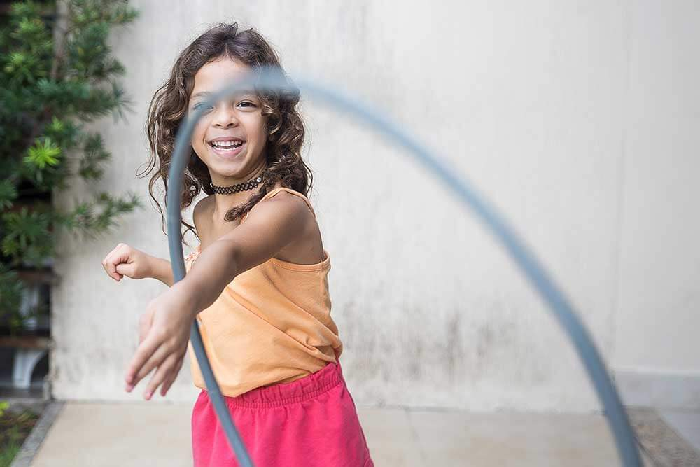 A smiling young girl throwing a hula hoop toward the camera